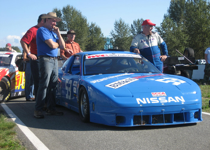 Andy Pearson and Collin Jackson stand near the /53 blue Nissan 240SX before podium presentation