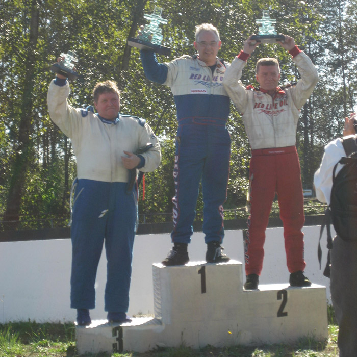 podium presentation with Collin Jackson in first place and Dave Humphrey in second place holding glass trophies