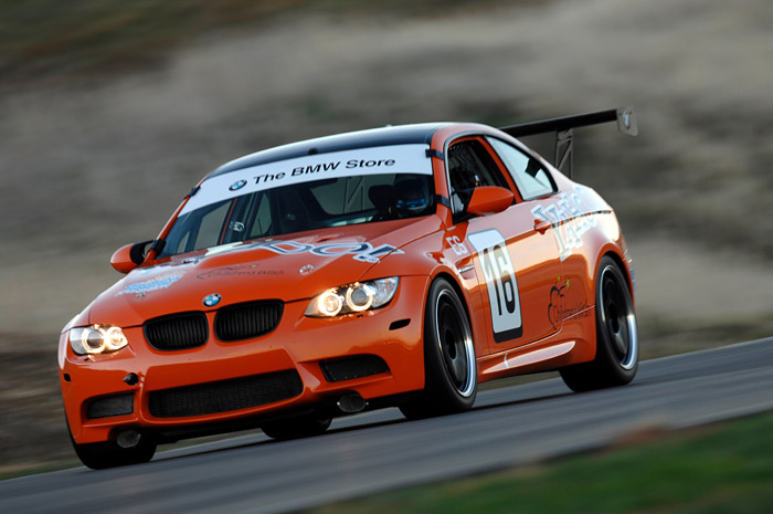 stylized closeup photo on diagonal angle of orange BMW race car driving down the track with the BMW Store written on the windshield