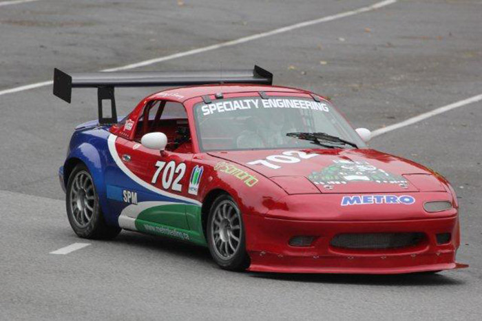 red, blue, green and white miata turbo racecar turning the corner