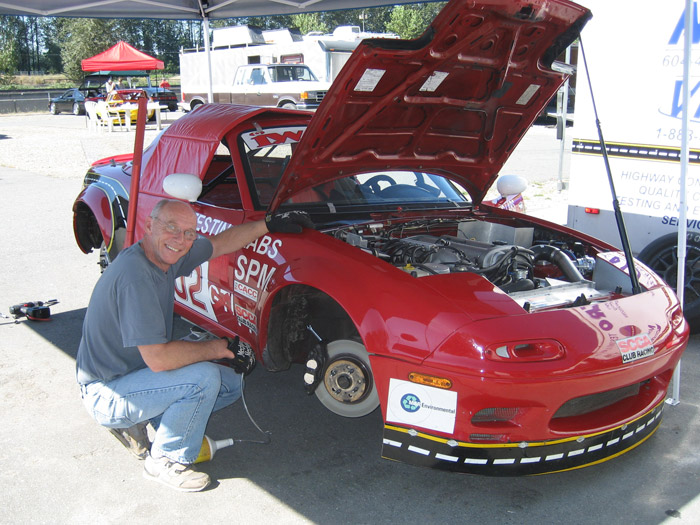mechanic nealihng by red Mazda Miata race car with the wheels off and working on the brakes
