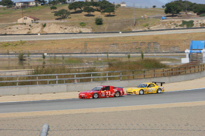 Dave Humphrey in his #73 red Nissan 240SX race car leads a yellow car just after a turn