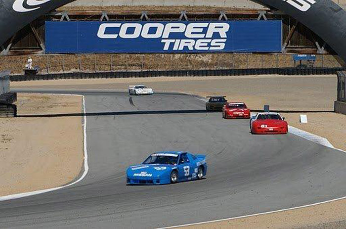 Collin Jackson in his #53 blue Nissan 240SX race car leads coming into a turn