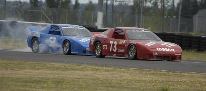 red #73 Nissan 240SX race car of Dave Humphrey just in front of blue #53 race car of Collin Jackson. Smoke comes from the tires of the blue race car