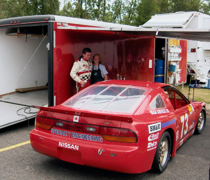 Dave Humphrey with his wife Stephanie Humphrey standing by the red Nissan 240SX racing car