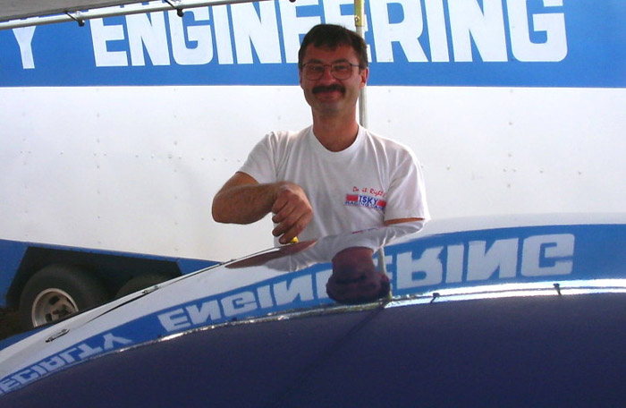 Steve Majchrzak smiling while working on Camaro of Andy Pearson. Specialty Engineering words can be seen in the reflection of the blue race car