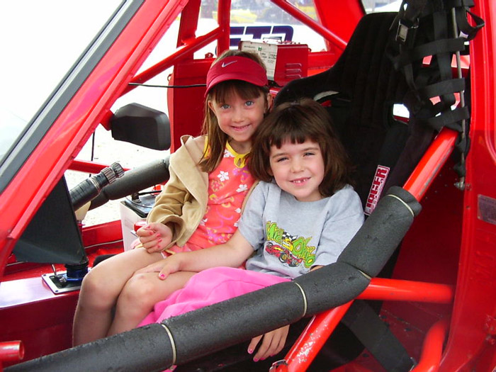 Two young girls smile while in the drivers seat of the red Datsun 510