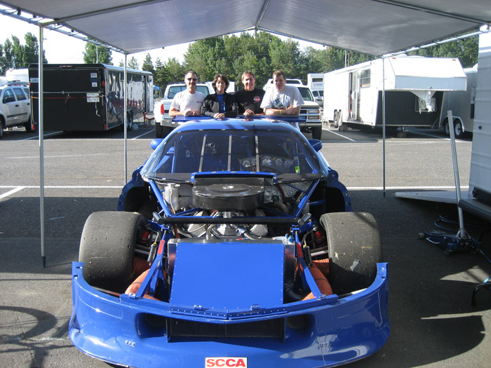 Specialty Engineering blue GT1 Camaro with hood off and racing engine exposed. Andy Pearson, Tracey Pearson and their crew pose behind the race car